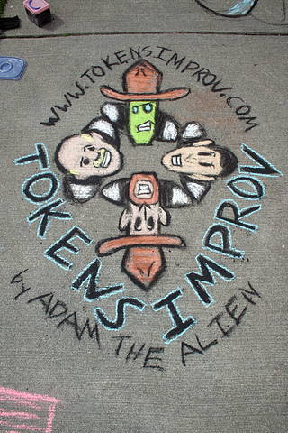A chalk depiction of The Tokens comedy improv group, by Adam the Alien.