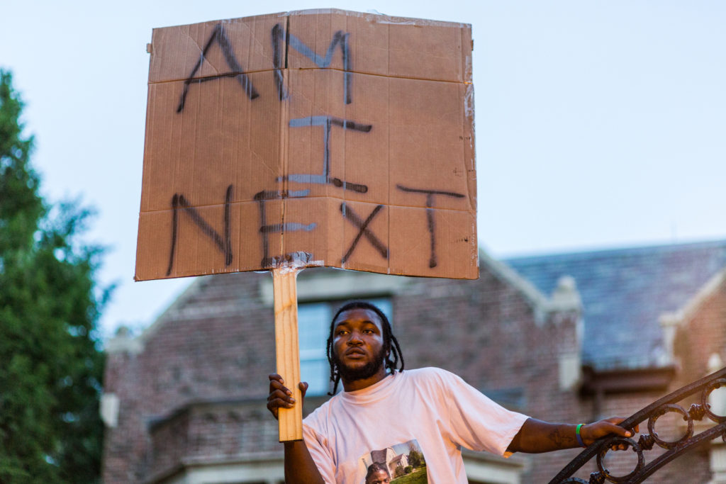 "A Black Lives Matter protester holds a sign asking, ""Am I next?"" The protest —held in Saint Paul, Minnesota on July 7th, 2016— was responding both to the recent publicized deaths of Philando Lee and Alton Sterling, as well as to the pervasive and systemic problems that led to the two black men being killed by police officers in what is increasingly recognized as an all too common occurrence. Photo by Tony Webster."